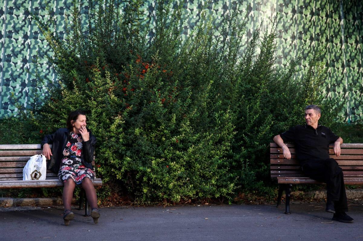ljudo sede na dve odvojene klupe