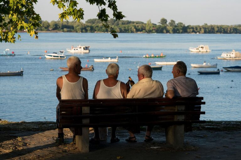 penzioneri sede na klupi na keju pored dunava
