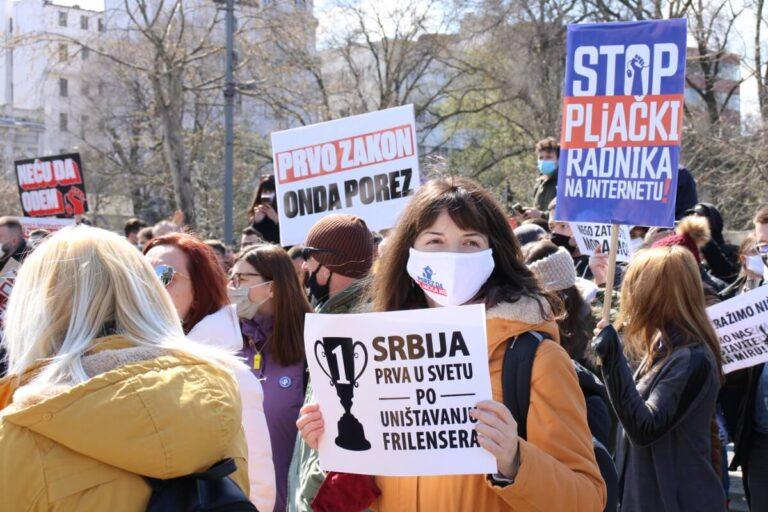 Demonstratkinja sa transparentom na protestu frilensera