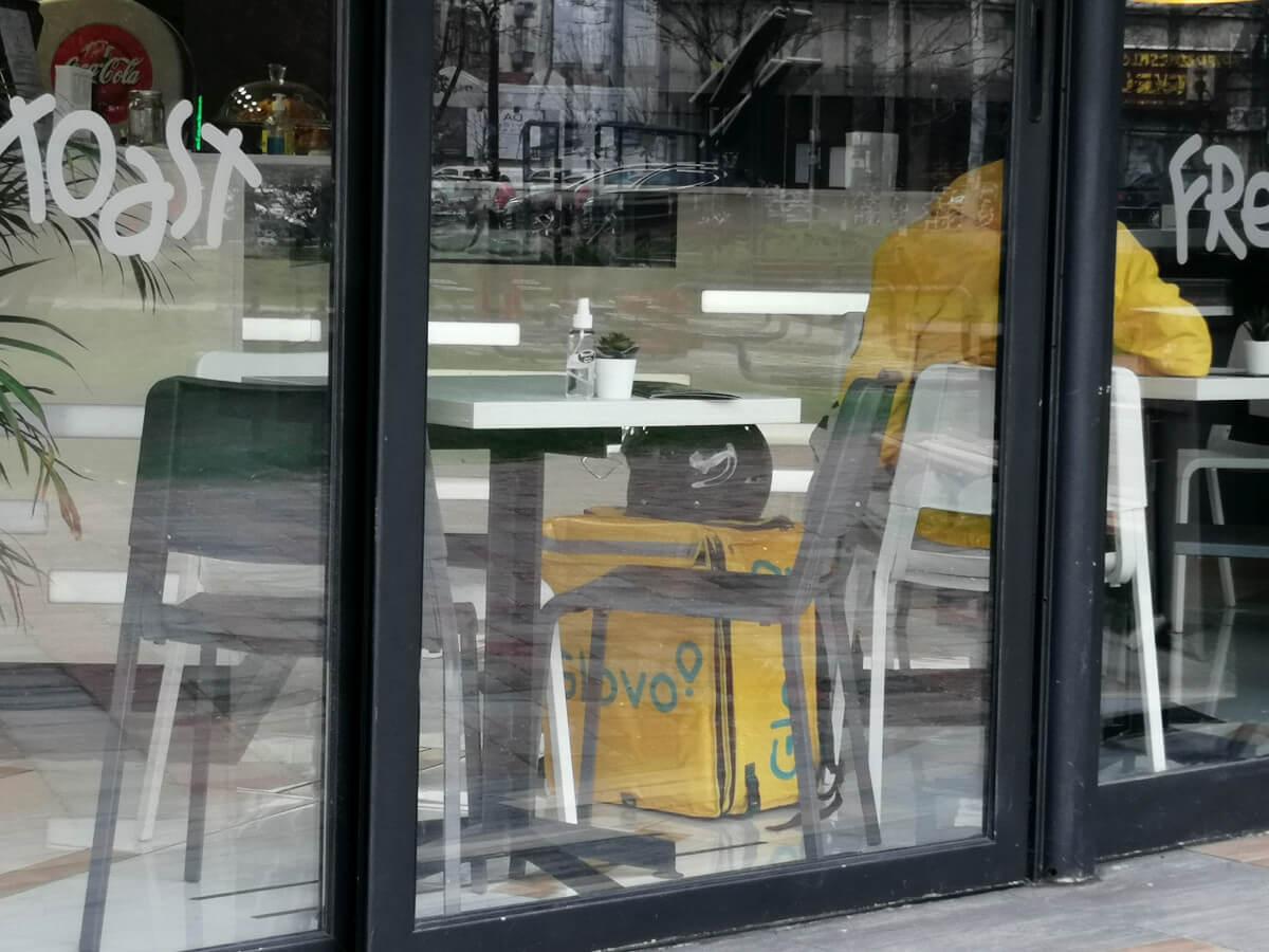 dostavljač Glova čeka da preuzme dostavu i jednom restoranu